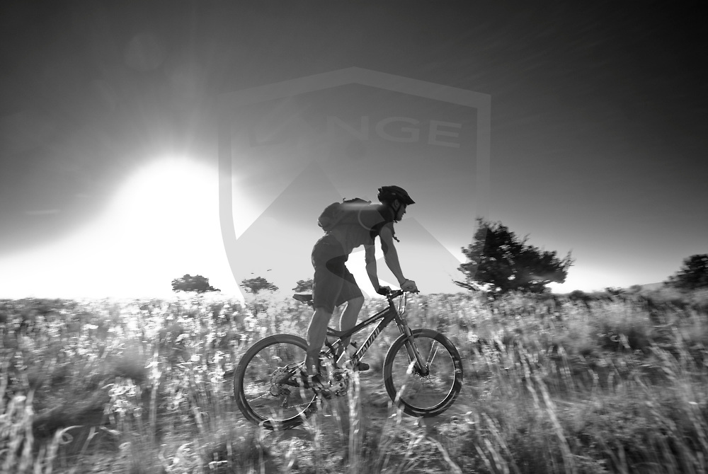 silhouette mountain biker sunshine landscape in black and white while riding at the white mesa bike trails of new mexico.  rider cliff younberg enjoys the beautiful nature scenery.