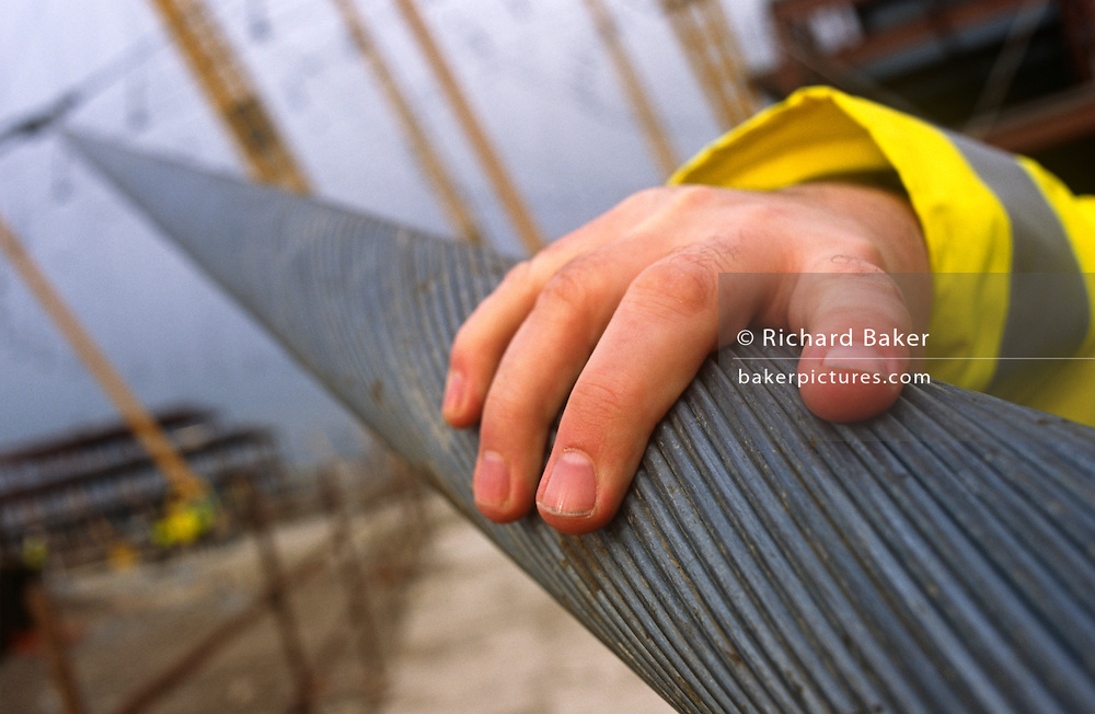 Detail of a hand restiing on a strong, wide cable strut during construction of the Millennium Dome.