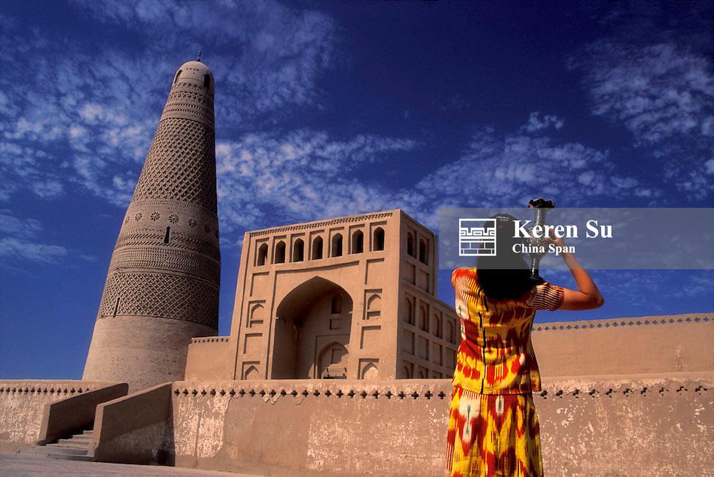 Uighur girl carrying a jar in front of Emin Minaret, Turpan, Xinjiang Province, Silk Road, China