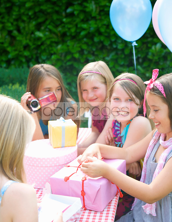 Smiling young girl sitting with friends opening a birthday gift