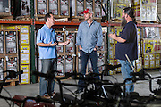 01/14/2016 132302 -- Garland, TX -- &copy; Copyright 2016 Mark C. Greenberg<br /> <br /> From left: President and COO Rick Sukkar and CEO Alex Keechleof talk with warehouse manager Kevin Sadler in the warehouse of Garland, Texas based Monster Moto