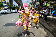 "05 JULY 2014 - BANGKOK, THAILAND:  School children on Sukhumvit Road in Bangkok during a parade for vassa. Vassa, called ""phansa"" in Thai, marks the beginning of the three months long Buddhist rains retreat when monks and novices stay in the temple for periods of intense meditation. Vassa officially starts July 11 but temples across Bangkok are holding events to mark the holiday all week.   PHOTO BY JACK KURTZ"