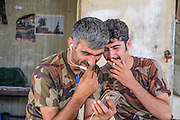 Peshmerga fighters enjoy a video conversation with friends back home, from the Mount Batiwa frontline. Iraqi Kurdistan.