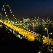 Traffic streaming over the Oakland Bay Bridge across San Francisco Bay at night with San Francisco Skyline in distance, San Francisco, California, USA
