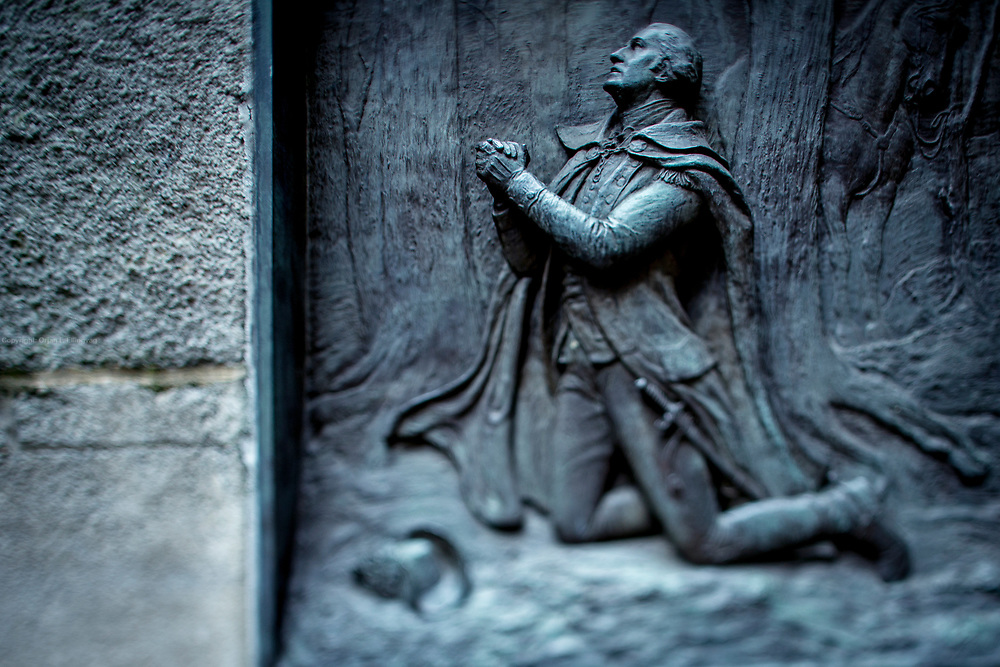 A brass relief of George Washington kneeling in prayer at Valley Forge. The relief, made by artist James E. Kelly in 1904, is on the side of the stairs leading to the Federal Hall near Wall Street, where George Washington was sworn in as Americas first President.