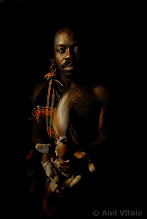 "Ahmad Msham, 39, a bush doctor from Chidodo settlement in Lindi, Tanzania holds a gourd with lion's hair that he uses for ""white magic"" when spirit lions are thought to be eating villagers. (Photo by Ami Vitale)"
