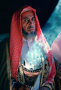 A Bedouin man in his tent holding an incense burner in Riyadh, Saudi Arabia