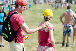 © Licensed to London News Pictures. 25/06/2015. Pilton, UK. Festival atmosphere at Glastonbury Festival 2015 on Thursday Day 2 of the festival. A man applies suncream to his girlfriends back on a hot sunny morning. This years headline acts include Kanye West, The Who and Florence and the Machine, the latter having been upgraded in the bill to replace original headline act Foo Fighters.   Photo credit: Richard Isaac/LNP