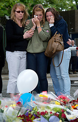 © London News Pictures. 25/05/2013. Woolwich, UK. Aimee West The  soldier girlfriend (centre green top) of Drummer Lee Rigby being comforted by friends and servicemen as she lays flowers at the scene of his death in Woolwich, London. Drummer Lee Rigby was murdered by two men in Woolwich town centre in what is being described as a terrorist attack. Photo credit: Ben Cawthra/LNP