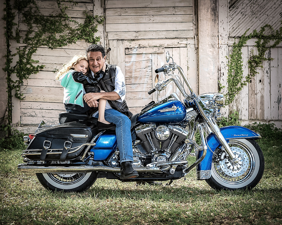 location portrait of man with granddaughter seated on motorcycle.