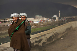 Bearded men walk along the Kabul river in Kabul, Afghanistan.