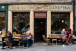 Exterior view of people in trendy The Milkman cafe on Cockburn Street in Edinburgh Old Town, Scotland, UK