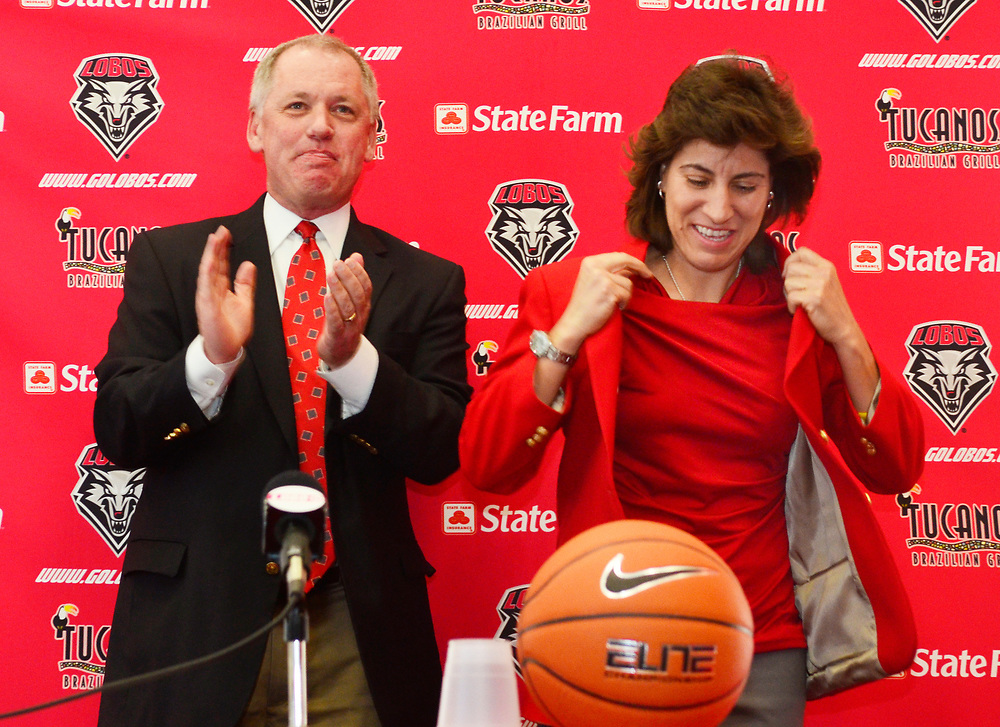 Yvonne Sanchez (Cq) was named on Friday April 22, 2011, head Women's Basketball Coach at the University of New Mexico.   Pictured is Sanchez (Cq), right, trying on the famous red jacket handed to her by  UNM's Director of Athletics Paul Krebs (Cq) during a press conference held at the Pit in Albuquerque, New Mexico.  <br /> Albuquerque, New Mexico. (Albuquerque Journal / Roberto E. Rosales.