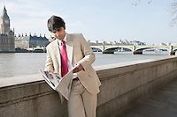 Indian businessman reading newspaper with buildings in background