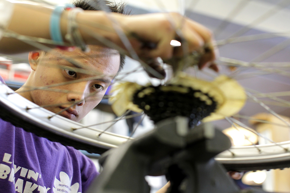 Youth Express apprentice Koua Yang, 15, fixes a wheel from a donated bicycle at Express Bike Shop in St. Paul, Minnesota.  By refurbishing and selling bicycles, youth apprentices learn mechanical, business, and entrepreneurial skills. All proceeds from bike sales go towards funding the program.