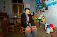 Elderly farmer sitting in farmhouse kitchen in village of Poli near Penglai, Shandong Province, China