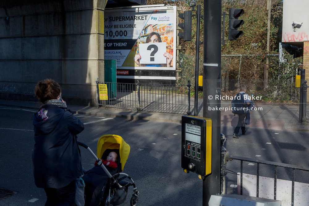 A mother waits to walk 0ver a crossing opposite a question mark in the context of a billboard ad at East Dulwich, on 14th February 2019, in London, England.