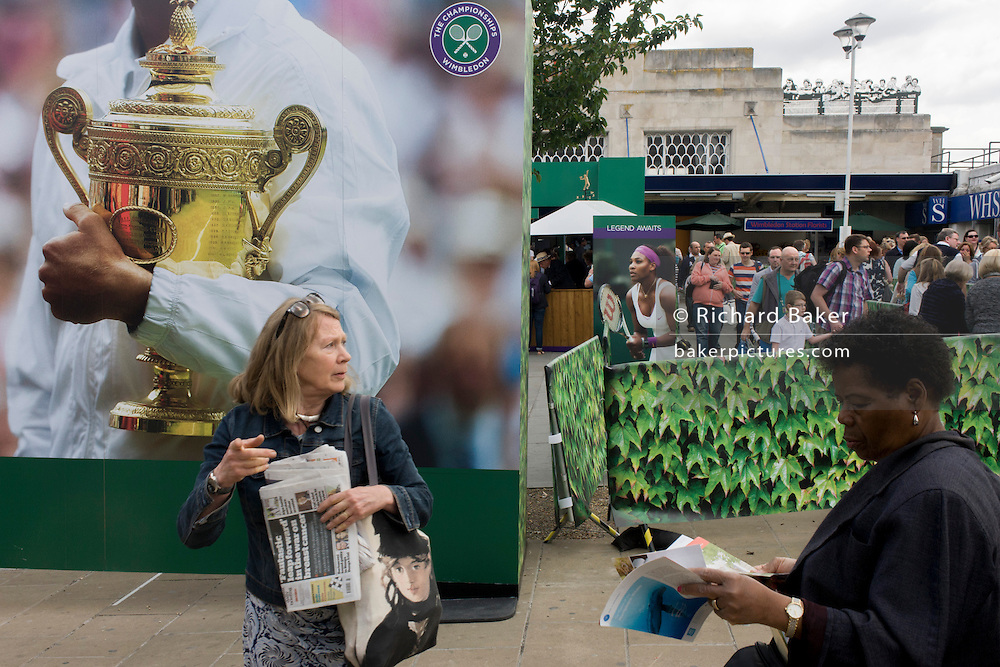 Day 2 of the annual lawn tennis championships and spectators mingle with locals near a large champions trophy billboard, outside the mainline and underground (subway) station in the south London suburb. The Wimbledon Championships, the oldest tennis tournament in the world, have been held at the nearby All England Club since 1877.