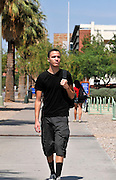 A young man walks on a college campus.
