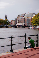 Amsterdam, Holland. Young man sitting at the edge of a canal with a view to the city.