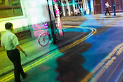 Seen through the abstract coloured mirrored glass of a backstreet bar, an unsighted pedestrian negotiates the road.