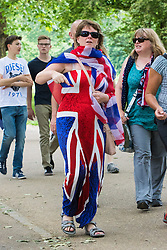 Green Park, London, June 11th 2016. Marking Her Majesty The Queen's official birthday, the Royal King's Horse Artillery fires a 41-Gun-Salute in Green Park. PICTURED: A woman wearing a Union Jack dress makes her way through the crowds in Green Park.