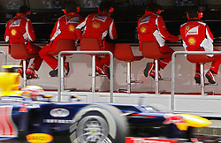epa03182316 Australian Formula One driver Mark Webber of Red Bull Racing drives his car past Scuderia Ferrari's team members during a practice session at the Shanghai International circuit in Shanghai, China, 14 April 2012. The 2012 Chinese Formula One Grand Prix will take place on 15 April.  EPA/HOW HWEE YOUNG