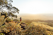A Maasai Warrior and guide, poses looking over the Maasai Mara at dawn. Photo by Greg Funnell.