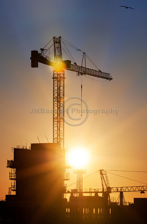 Sunrise bursts behind construction crane in Montreal Canada