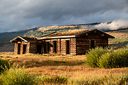 """Abandoned cabin. Green River Lakes, Wind River Range, Bridger-Teton National Forest, Rocky Mountains, Wyoming, USA. The Continental Divide follows the crest of the """"Winds""""."""