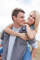 Happy young man giving piggyback ride to woman on field