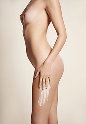 Side View of Nude Woman Applying Body Lotion on Thigh