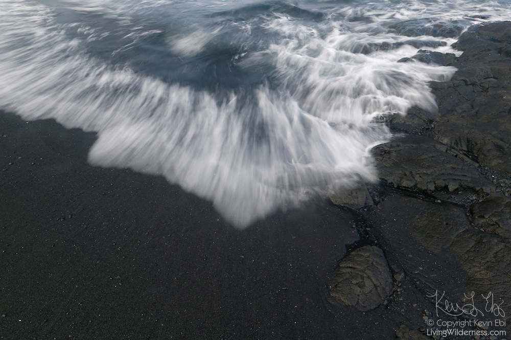 Pacific Ocean waves crash onto the Punalu`u Black Sand Beach on the Big Island of Hawaii. The beach is near the Volcanoes National Park and the erosion from the ocean waves turns the volcanic rock into black sand.