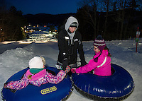 Cameron Haradon helps Kendra and Olivia at the start of the tubing hill during the Boys and Girls Club's Tubing Party at Gunstock on Sunday evening.  (Karen Bobotas/for the Laconia Daily Sun)