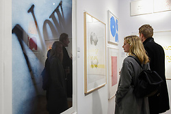 "© Licensed to London News Pictures. 03/05/2017. London, UK. Visitors cast a reflection in a work called ""Now"", 1990, by Ed Ruscha at the preview of the 32nd London Original Print Fair at the Royal Academy of Arts in Piccadilly.  51 international specialist dealers are presenting works in the print medium to buyers from 4 May to 7 May. Photo credit : Stephen Chung/LNP"