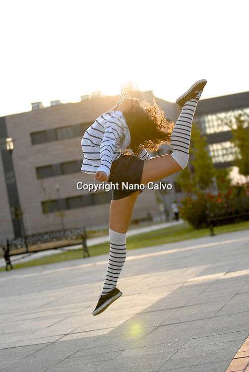 Young woman performing artistic jumps at sunset