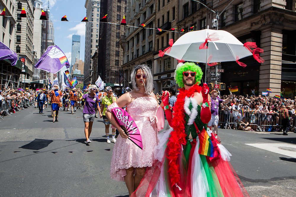 "New York, NY - 30 June 2019. The New York City Heritage of Pride March filled Fifth Avenue for hours with participants from the LGBTQ community and it's supporters. Two men in dresses, one of who carries a fan that reads ""Bitchy."""