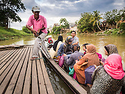 16 JUNE 2015 - SUNGAI KOLOK, THAILAND:  People from Malaysia get off a small boat on the Thai side of the border. The border between Thailand and Malaysia in Sungai Kolok, Narathiwat, Thailand. Thai and Malaysians cross the border freely for shopping and family visits. The border here is the Kolok River (Sungai is the Malay word for river).        PHOTO BY JACK KURTZ