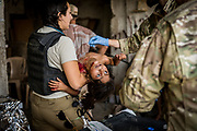 Katie Batrouney, a paramedic from Australia, carries an injured child to an ambulance after providing pre-hospital care at a trauma stabilisation point set up inside an abandoned store on the edge of Mosul's Old City on June 21, 2017.