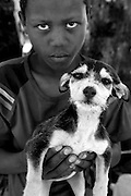 A boy is photographed with his puppy while he waits for it to receive treatment at a mobile clinic in Soul City, South Africa.  IFAW's CLAW program, provides veterinary services to cats and dogs in some of the poorest shantytowns outside of Johannesburg, South Africa.