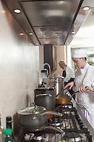 Two chefs work in kitchen
