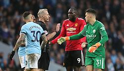 Manchester City goalkeeper Ederson (right) and Manchester United's Romelu Lukaku talks to Referee Martin Atkinson