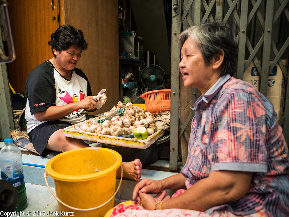 18 SEPTEMBER 2015 - BANGKOK, THAILAND: SANONG NOYMHA, 48, peels garlic and chats with her neighbor in front of her shop in the Wat Kalayanamit neighborhood. Both women are being evicted from their homes. Fiftyfour homes around Wat Kalayanamit, a historic Buddhist temple on the Chao Phraya River in the Thonburi section of Bangkok, are being razed and the residents evicted to make way for new development at the temple. The abbot of the temple said he was evicting the residents, who have lived on the temple grounds for generations, because their homes are unsafe and because he wants to improve the temple grounds. The evictions are a part of a Bangkok trend, especially along the Chao Phraya River and BTS light rail lines. Low income people are being evicted from their long time homes to make way for urban renewal.             PHOTO BY JACK KURTZ