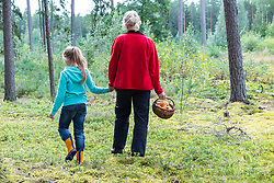 Family in forest. Mother and daughter holding basket of mushrooms.
