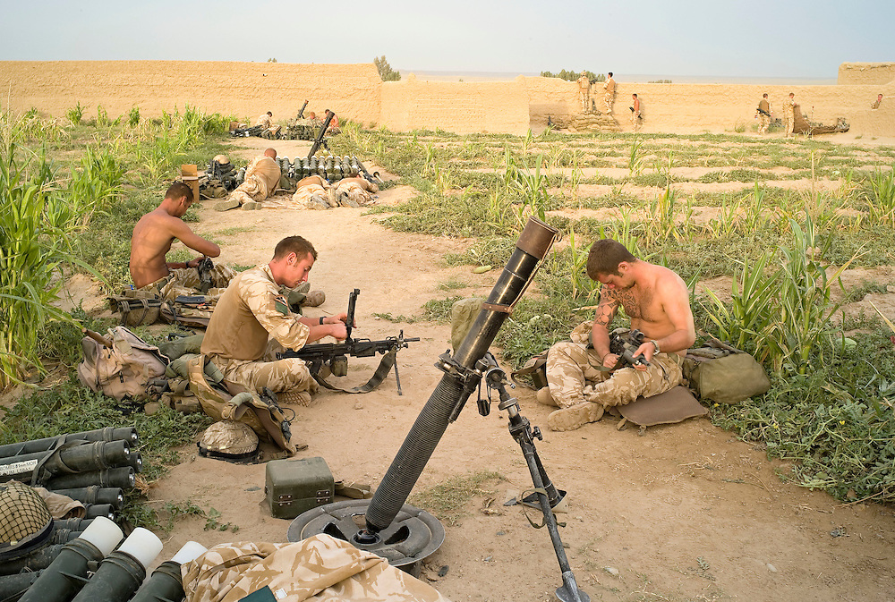 British soldiers of 3rd Battalion The Parachute Regiment rest, eat or clean weapons between missions from their temporary patrol base after an airborne assault as part of Operation 'Southern Beast'. Kandahar Province, Afghanistan on the 4th of August 2008.