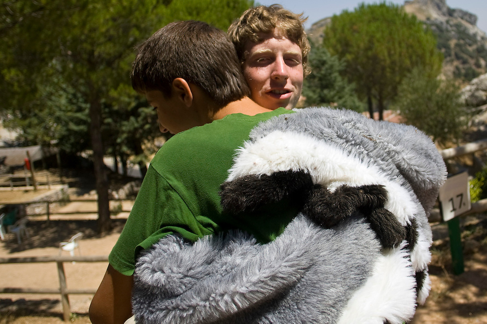(Grazelema, Spain - July 31, 2010) - On departures day at Little Village in Grazelema a camper says goodbye to James, who had dressed in the owl costume to greet parents. ..Photo by Will Nunnally / TECS