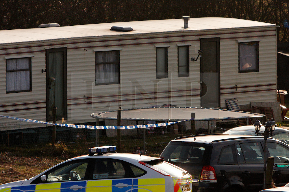 © Licensed to London News Pictures.  01/02/2012. STANWELL MOOR, UK. A police car guards the scene outside a caravan on Lower Mill Farm, Stanwell Moor near Heathrow. A man, thought to be in his 50s, was shot and killed at 10:10pm last night (Tuesday). A woman has been arrested. Photo credit :  Cliff Hide/LNP