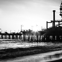 Santa Monica Pier panorama black and white photo. Panorama photo ratio is 1:3 and  incudes the sun setting over Santa Monica Pier and Ferris Wheel along the Pacific Ocean in Los Angeles County Southern California.