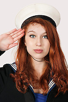 Portrait of young woman in sailor's uniform saluting against gray background