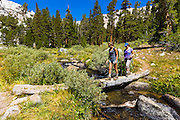 Hikers crossing footbridge in the Big Pine Lakes basin, John Muir Wilderness, California USA